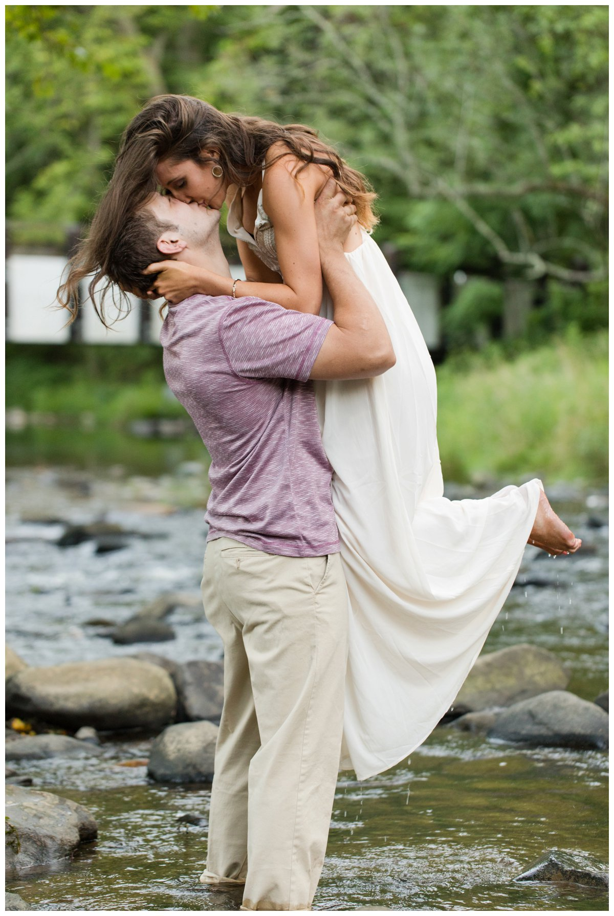 Jerusalem Mills Bohemian Engagement Photography in a stream in a white dress. He is lifting her and Kissing her. Water is dripping from her feet.