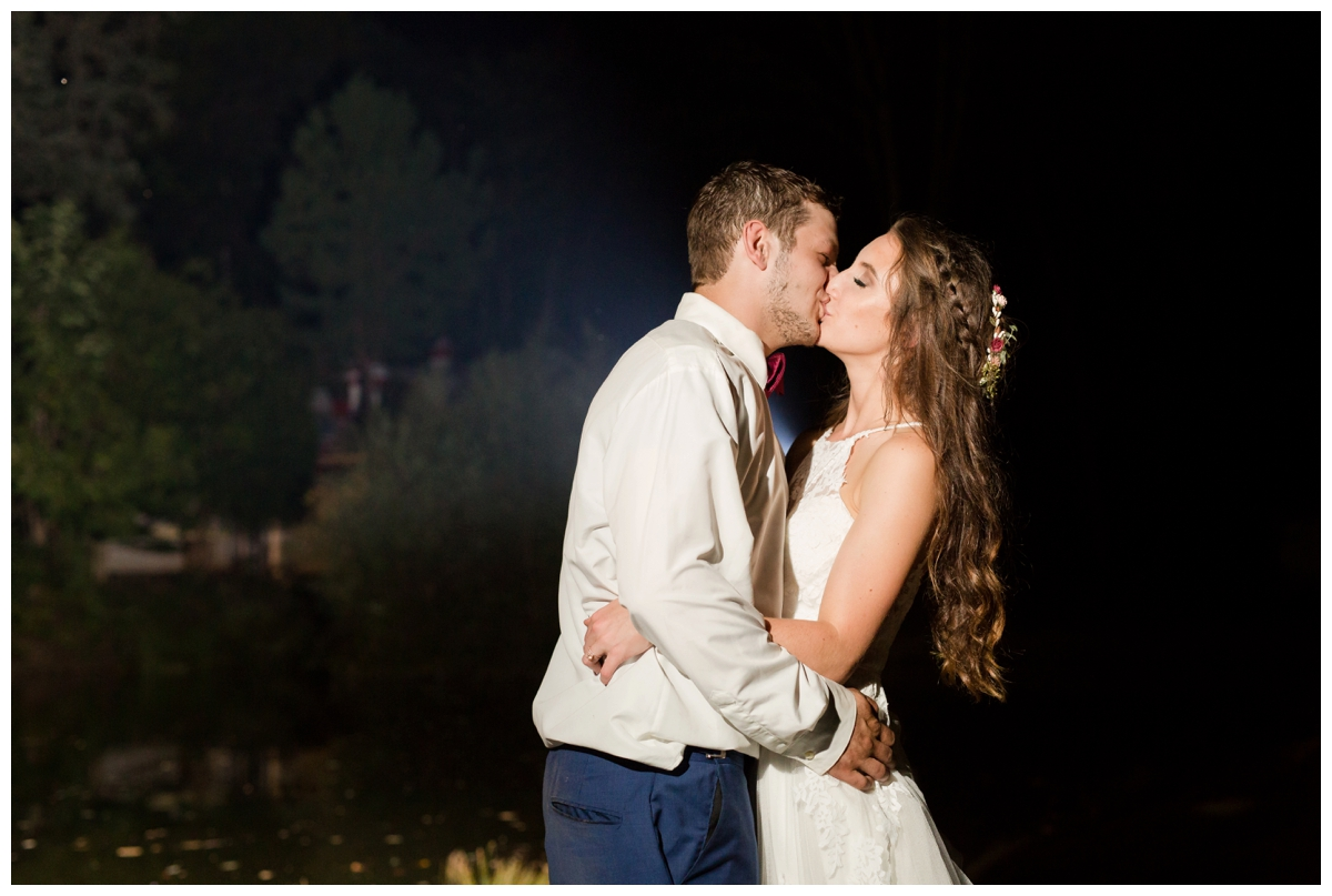 Night photo of bride and groom backlit by the pond