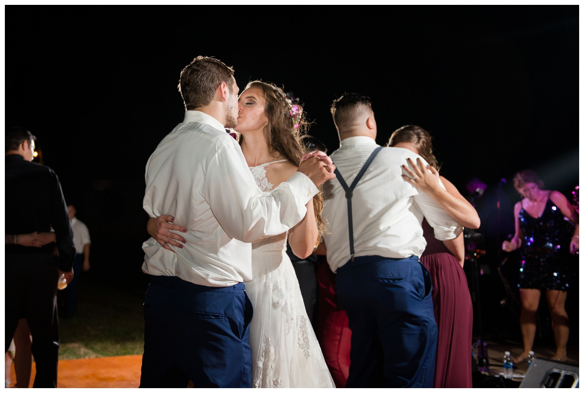 Bride and groom kissing on the dance floor at outdoor wedding at night