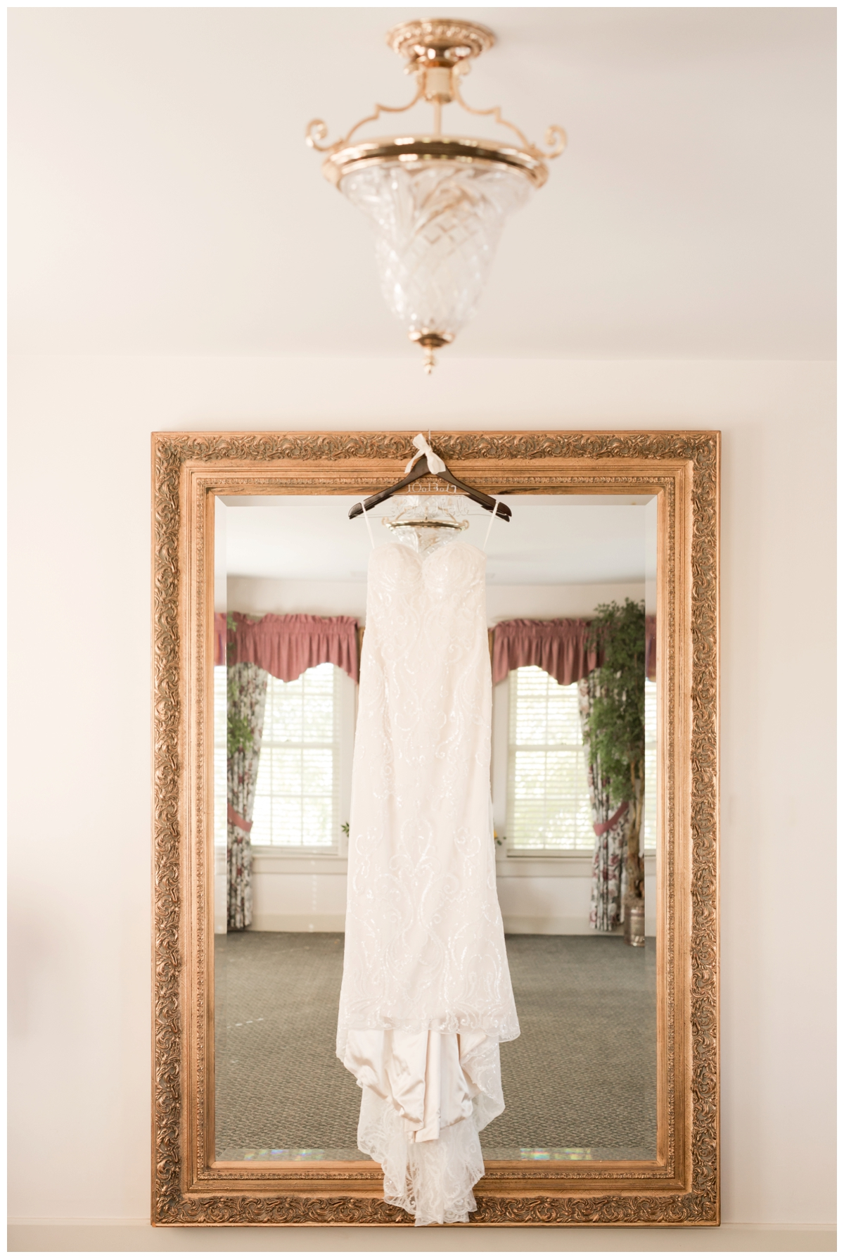 Bride's wedding dress hanging on a mirror with lace details
