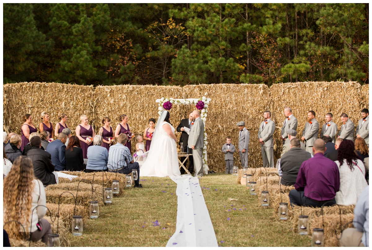 Couple being married in front of a wall of hay bales