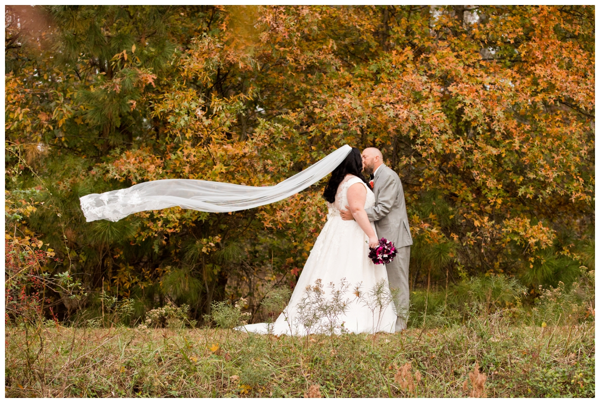 Fall portrait of bride and groom surrounded by trees and veil blowing in the wind. Veil shot.
