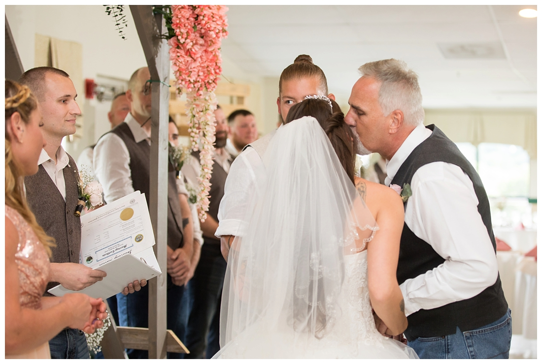 Indoor wedding ceremony. Bride's father giving her away to the groom. Father kissing the bride. Maryland wedding at Circle D Farm in Woodbine. Maryland Wedding Photographer