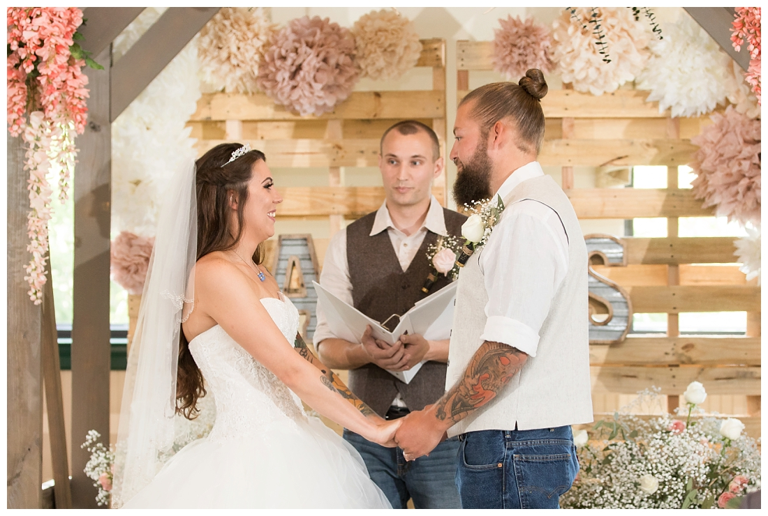 Indoor wedding ceremony. Rustic Wedding Decor. Rose Gold wedding decor. Wooden arbor with flowers. Maryland wedding at Circle D Farm in Woodbine. Maryland Wedding Photographer.