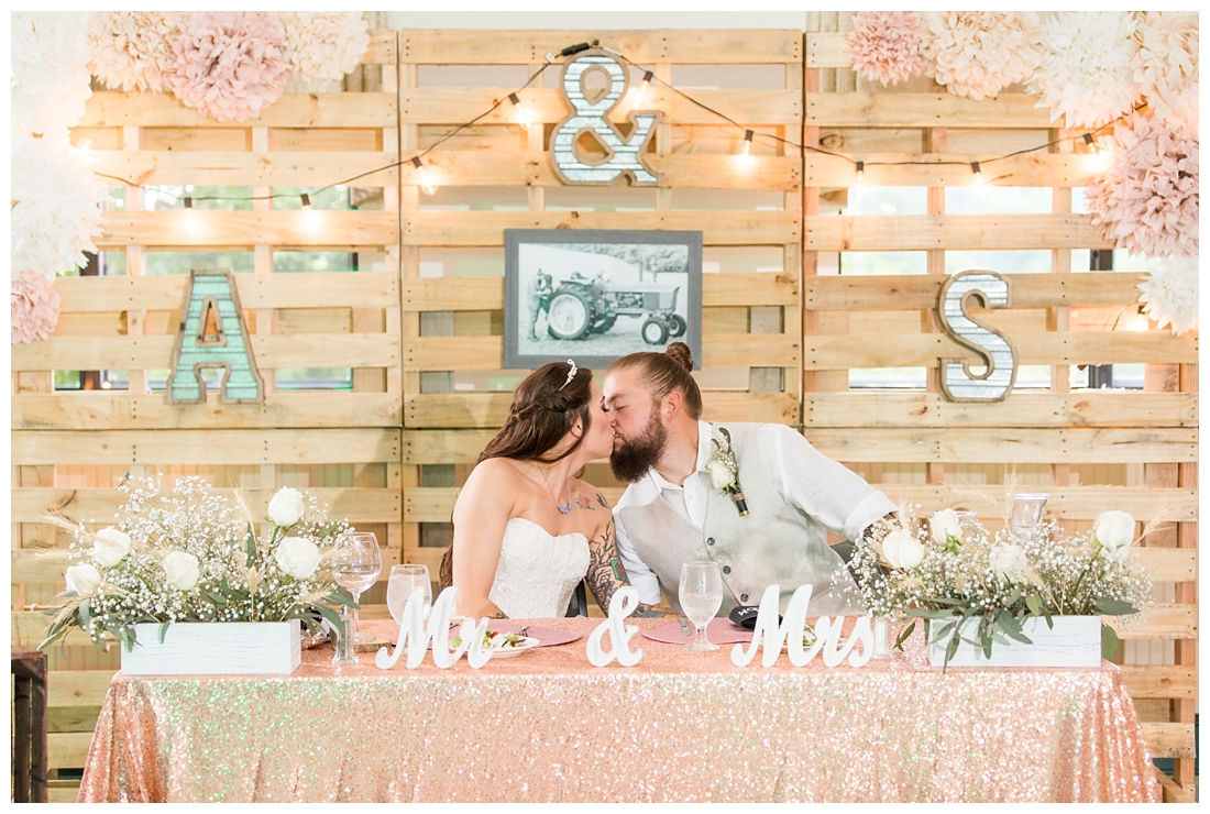 Bride and Groom kissing at sweetheart table with a pallet wall. Reception details and decor. Rustic wedding decor. Rose gold wedding decor. Maryland wedding at Circle D Farm in Woodbine. Maryland Wedding Photographer.