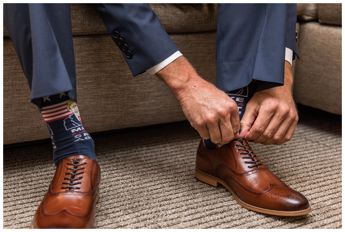 Winery at Bull Run Virginia Wedding. Bride and Groom married ar ruins in vineyards. Dusty Blue and Navy Wedding. Groom tying shoes wearing trump socks