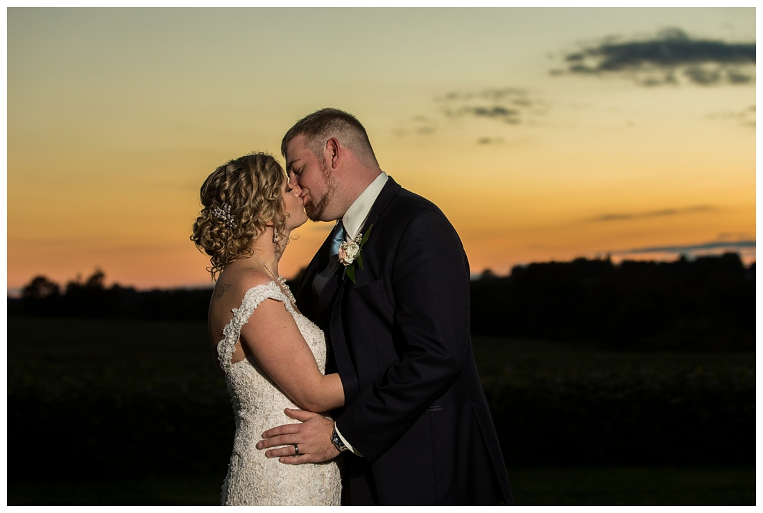 Fall wedding at The Royer House in Westminster Maryland. Cool fall day with dusty blue theme. Carroll County wedding. Cold Wedding day. Windy Wedding. Farm Wedding. Bride and groom at sunset on a farm. Bride and groom kissing. Sunset photos.